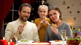 Famille gaie mangeant les biscuits traditionnels de Noël, regardant à la caméra, traditions images stock