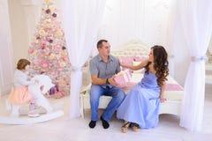 Famille gaie recueillie pour échanger des cadeaux de Noël dans s lumineux Image libre de droits