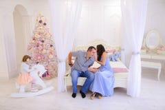 Famille gaie recueillie pour échanger des cadeaux de Noël dans s lumineux Images libres de droits