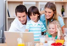 Famille gaie utilisant l'ordinateur portatif pendant le déjeuner photo stock