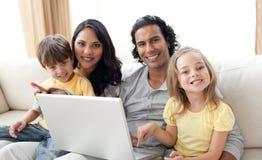 Famille gaie utilisant l'ordinateur portatif sur le sofa Photo stock