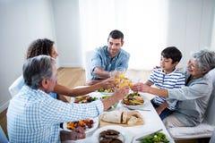 Famille grillant des verres de jus d'orange tout en prenant le petit déjeuner Photo libre de droits