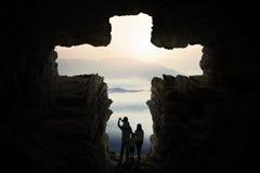 Famille heureuse à l'intérieur de signe croisé formé par caverne Photographie stock