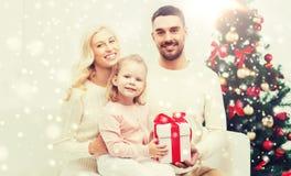 Famille heureuse à la maison avec le boîte-cadeau de Noël Images stock