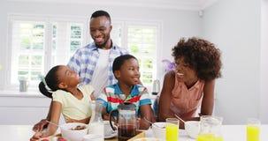 Famille heureuse à la table de petit déjeuner banque de vidéos