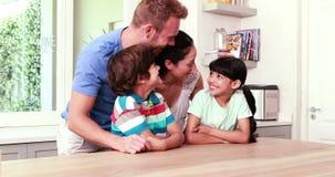 Famille heureuse étreignant dans la cuisine banque de vidéos