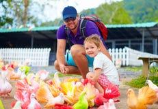 Famille heureuse alimentant les oiseaux colorés de pigeon à la ferme Image libre de droits
