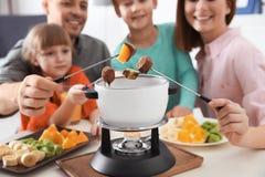 Famille heureuse appr?ciant le d?ner de fondue ? la maison photo stock
