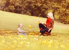 Famille heureuse au jour ensoleillé d'automne, mère jouant avec son enfant images stock