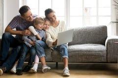Famille heureuse avec de petits enfants appréciant à l'aide du pouvoir adiathermique d'ordinateur portable Photographie stock libre de droits