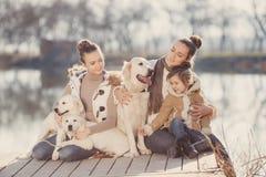 Famille heureuse avec des animaux familiers près du lac Image libre de droits