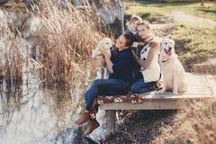 Famille heureuse avec des animaux familiers près du lac Photos stock