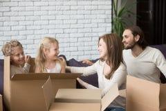 Famille heureuse avec des boîtes en carton à leur nouvelle maison photos stock