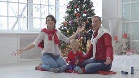 Famille heureuse avec des confettis sur le fond de l'arbre de Noël avec des cadeaux clips vidéos