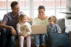 Famille heureuse avec des enfants ayant l'amusement utilisant l'ordinateur portable sur le sofa Images stock