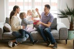 Famille heureuse avec des enfants félicitant le papa enthousiaste avec les pères d photographie stock libre de droits
