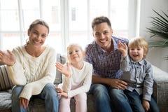 Famille heureuse avec des enfants ondulant la main regardant l'appareil-photo, portrait Images libres de droits