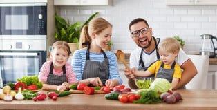 Famille heureuse avec des enfants préparant la salade végétale Image stock