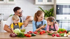 Famille heureuse avec des enfants préparant la salade végétale Photo stock