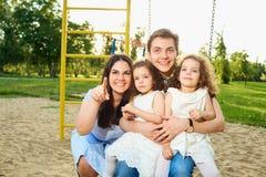 Famille heureuse avec des enfants sur une oscillation au terrain de jeu Photographie stock