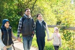 Famille heureuse avec des sacs à dos augmentant en bois image libre de droits