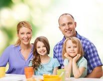 Famille heureuse avec deux enfants avec prendre le petit déjeuner Photos stock