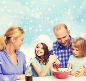 Famille heureuse avec deux enfants faisant la salade à la maison Images stock