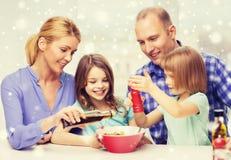 Famille heureuse avec deux enfants faisant la salade à la maison Photographie stock libre de droits