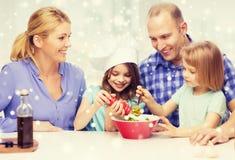 Famille heureuse avec deux enfants faisant la salade à la maison Image stock
