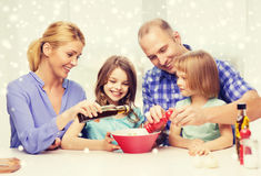 Famille heureuse avec deux enfants faisant la salade à la maison Photo libre de droits