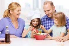Famille heureuse avec deux enfants faisant le dîner à la maison images libres de droits