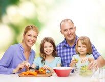 Famille heureuse avec deux enfants faisant le dîner à la maison Images stock