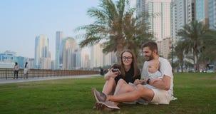 Famille heureuse avec deux enfants s'asseyant ensemble sur l'herbe en parc et prenant un selfie Avec le smartphone banque de vidéos