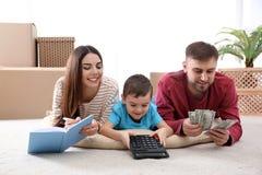 Famille heureuse avec l'argent sur le plancher images libres de droits
