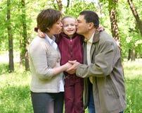 Famille heureuse avec l'enfant en parc d'été, à lumière du soleil, herbe verte et arbres Photographie stock