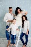 Famille heureuse avec la femme enceinte et les enfants posant dans le studio photos stock