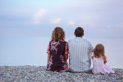 Famille heureuse avec la fille s'asseyant sur la plage, par le dos Images libres de droits