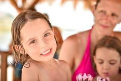 Famille heureuse avec la petite fille souriant et mangeant la crème glacée  Image stock