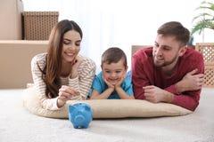 Famille heureuse avec la tirelire et l'argent sur le plancher image libre de droits