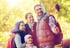 Famille heureuse avec le bâton de selfie de smartphone au camp Photographie stock libre de droits