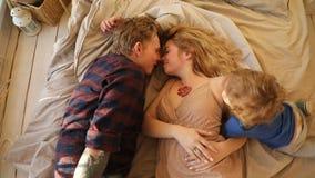 Famille heureuse avec le bébé sur le lit banque de vidéos