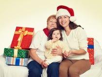 Famille heureuse avec le cadeau de boîte, la femme avec l'enfant et les personnes âgées - concept de vacances Images libres de droits