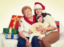 Famille heureuse avec le cadeau de boîte, la femme avec l'enfant et les personnes âgées - concept de vacances Image stock