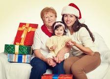Famille heureuse avec le cadeau de boîte, la femme avec l'enfant et les personnes âgées - concept de vacances Photo stock
