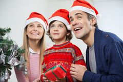 Famille heureuse avec le cadeau de Noël regardant loin Photo stock