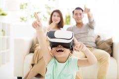Famille heureuse avec le casque de réalité virtuelle dans le salon Photographie stock libre de droits