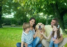Famille heureuse avec le chien appréciant en parc Photographie stock