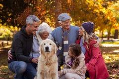 Famille heureuse avec le chien au parc pendant l'automne Photographie stock libre de droits