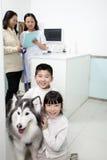 Famille heureuse avec le chien dans le bureau du vétérinaire Images libres de droits