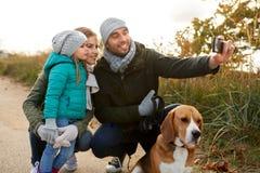 Famille heureuse avec le chien prenant le selfie en automne image stock